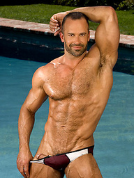Big hairy bodybuilder posing by the pool